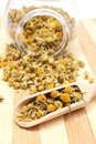Dried chamomile in glass jar and on wooden spoon closeup of pouring out of heap of Royalty Free Stock Photos