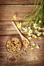 Dried chamomile tea with fresh chamomile flowers on rustic wooden table Stock Photos