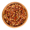 Dried chili pepper flakes in wooden bowl over white Royalty Free Stock Photo
