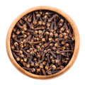 Dried cloves in a wooden bowl over white Royalty Free Stock Photo
