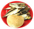 Dried fish and bread roll on red plate isolated white Royalty Free Stock Photography
