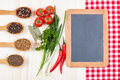 Dried and fresh food ingredients a blank blackboard or menu board on a red checkered tablecloth with red tomatoes chillies green Royalty Free Stock Images