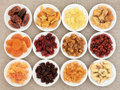 Dried fruit assortment in white porcelain bowls over hessian background Stock Photos
