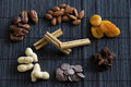 Dried fruit nuts chocolate and cinnamon apricots dates sultanas almonds peanuts drops on a black mat Royalty Free Stock Photography