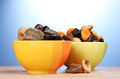 Dried fruits in bright bowls on wooden table Royalty Free Stock Images