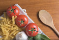 Dried fusilli pasta with tomatoes, basil, garlic and a wooden spoon Royalty Free Stock Photo