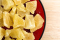 Dried pineapple chunks on red plate close view top of a serving of sugared a dish atop a wood table top Stock Photo