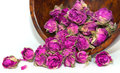 Dried pink and purple rose buds prepare for spa therapy wooden bowl filled with on white background Stock Image
