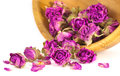 Dried pink and purple rose buds prepare for spa therapy wooden bowl filled with on white background Stock Photos