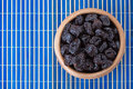 Dried prunes wooden bowl blue bamboo table cloth Stock Photography