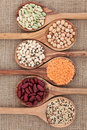 Dried pulses selection in olive wood spoons over hessian background Royalty Free Stock Photo