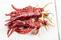 Dried red peppers on a white barnwood table Stock Image