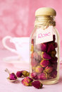 Dried rosebuds tea in a glass bottle of pink background Royalty Free Stock Photos