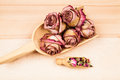 Dried roses and buds with wooden objects texture Stock Images