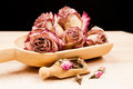 Dried roses and buds with wooden objects texture Royalty Free Stock Images