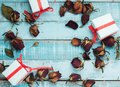 Dried roses with gift boxes on blue wooden parquet planks Royalty Free Stock Photo
