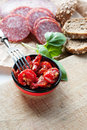 Dried tomatoes sun sliced salami bread and basil on a wooden table Stock Photography