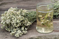 Dried yarrow and decoction for herbal medicine a bunch of in the glass jar on an old wooden table Royalty Free Stock Photo