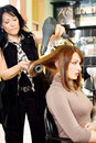 Dries hair in salon a professional hairdresser brunette with a dryer Royalty Free Stock Photography