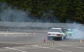 Drift cars performing simultaneous drifting Royalty Free Stock Photo