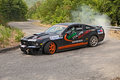 Drift racing car ford mustang a in action with smoking tires in hairpin bend at rally della romagna on july in dovadola fc italy Stock Image