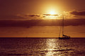 Drifting boat on a sunset and sailboat silhouette Stock Photos