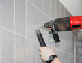 Drilling a marked tile wall to install bathroom fittings Stock Images
