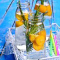 Drink with citrus and rosemary in a glass bottle water drops selective focus Royalty Free Stock Photography