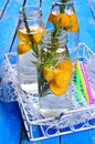 Drink with citrus and rosemary in a glass bottle water drops selective focus Stock Photo