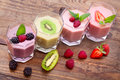 Drink smoothies four summer strawberry, blackberry, kiwi, raspberry on wooden table. Royalty Free Stock Photo