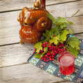 Drink of viburnum a glass with a cranberry on the background traditional ukrainian vessel kumanez and twigs on a wooden table Royalty Free Stock Photo