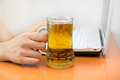 Drinking alcohol at the work woman working laptop and a tankard Royalty Free Stock Photo