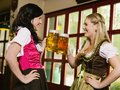 Drinking beer at oktoberfest photo of two beautiful women wearing traditional dirndl and Royalty Free Stock Image