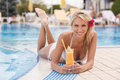 Drinking cocktail on the poolside. Attractive youn Royalty Free Stock Photo