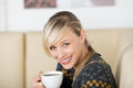 Drinking coffee happy blond woman at home Royalty Free Stock Images