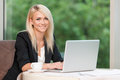 Drinking coffee at the restaurant smiling beautiful blond business woman with laptop Stock Photography