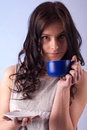 Drinking from a cup young beautiful woman blue Royalty Free Stock Photo