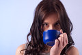Drinking from a cup young beautiful woman blue Stock Photos