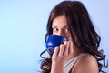 Drinking from a cup young beautiful woman blue Stock Photo