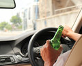 Drinking and driving beer or alcoho while a car Stock Photos