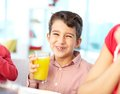 Drinking juice portrait of happy boy laughing while and looking at camera Stock Image