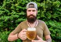 Drinking like a hipster. Hipster drinker holding beer mug. Bearded hipster enjoy drinking beer on nature. Hipster man Royalty Free Stock Photo