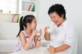 Drinking milk at home happy multi generations asian family beautiful grandmother and granddaughter healthcare concept Royalty Free Stock Photography