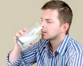 Drinking milk young man a glass of Royalty Free Stock Images