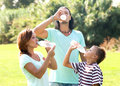Drinking from plastic bottles happy parents with son in summer park Royalty Free Stock Photo