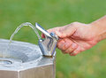 The drinking water faucet at public park man s hand turns on Stock Image