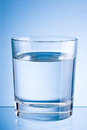 Drinking water glass on blue background a Stock Images