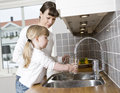 Drinking water small girl in the kitchen with her mother Stock Photography