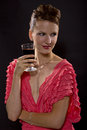 Drinking wine young woman wearing a pink dress and isolated on a black background Stock Photo