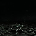 Dripping fluid, formed a dark crater, splashes and drops of water. Royalty Free Stock Photo